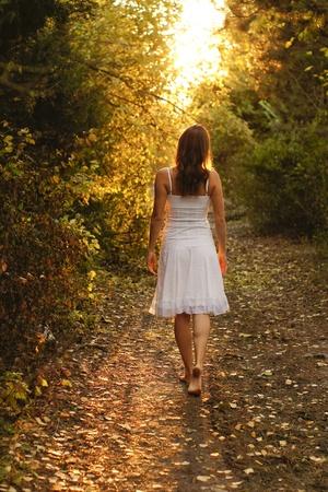 Niña con vestido blanco caminando por un camino misterioso en el bosque
