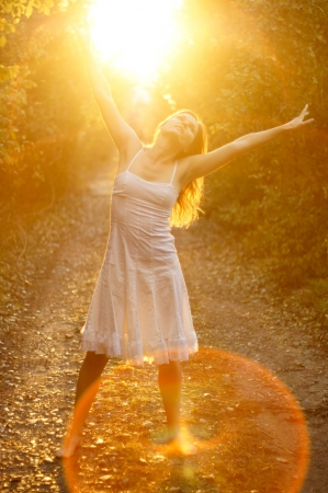 aura: Beautiful young girl dancing in the golden light of the setting sun on forest track Stock Photo