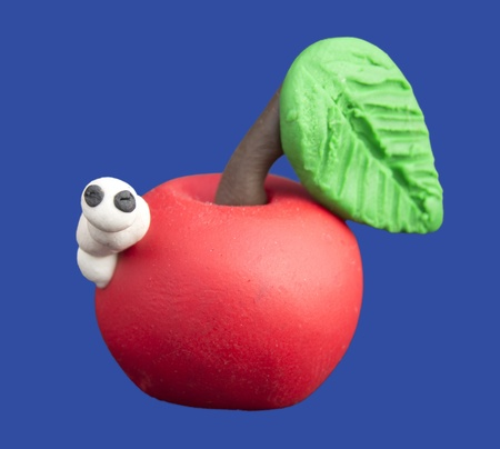 White worm peaks out of a red apple with green leaf made of plasticine Stock Photo
