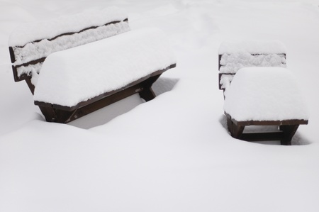 Two garden benches covered with thick layer of snow photo