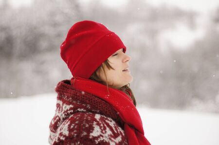 Beautiful young woman with red scarf and hat enjoying the snow photo