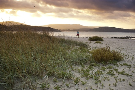 Lone girl walks across wild beach at dusk, photographing nature photo