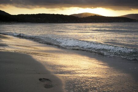unspoilt: A solitary footprint on a wild beach as the tide goes out Stock Photo
