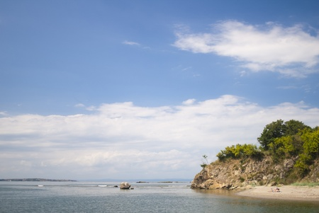 Two people lie on a secluded wild beach enjoying the tranquility and nature