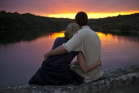 A couple gently embrace as the sun sets photo
