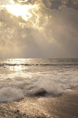 amanecer: Se rompe la luz del sol a través de las nubes celestiales sobre el mar