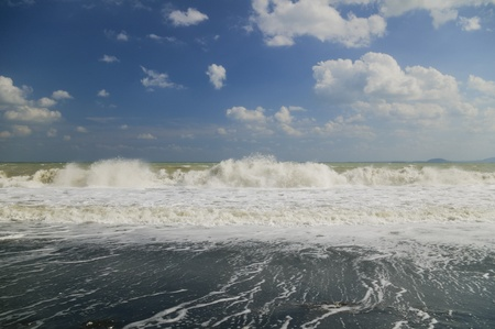 Beautiful waves crashing on a sandy beach on a clear day with blue sky and white clouds photo