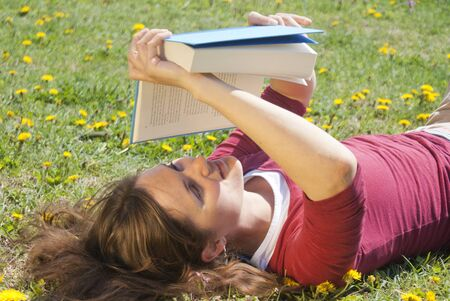 Beautiful young girl reading a book lying on a green meadow with dandelions  photo