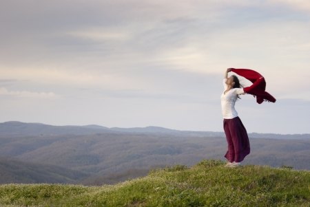 Beautiful young woman standing on top of mountain feeling empowered expressing joy and freedom photo