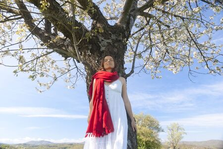 Beautiful young woman leaning on a cherry tree in bloom feeling one with Nature photo
