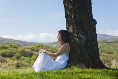 Beautiful young woman meditating under a cherry tree in bloom Stock Photo - 13254327