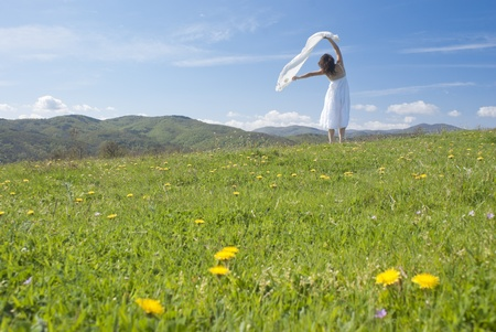 Beautiful young woman with a white dress enjoying the freedom of being outdoors in springtime