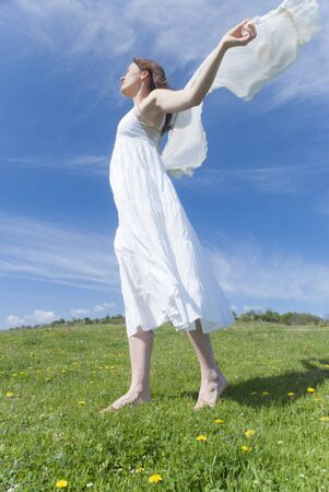 Beautiful young woman with a white dress enjoying the freedom of being outdoors in springtime photo