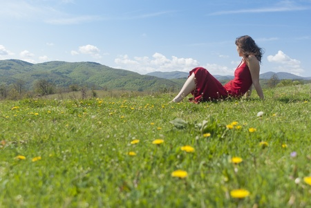 Beautiful young woman with red dress relaxing on a green meadow in springtime photo