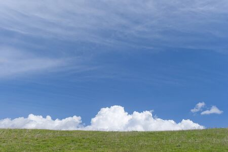 Blue sky, green meadow and white clouds on a bright sunny day photo