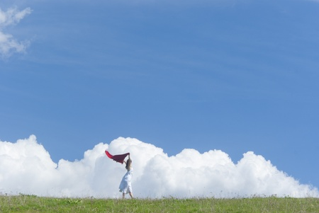 high spirits: Beautiful young girl with white dress enjoying the sunny day on a green meadow under the blue sky Stock Photo