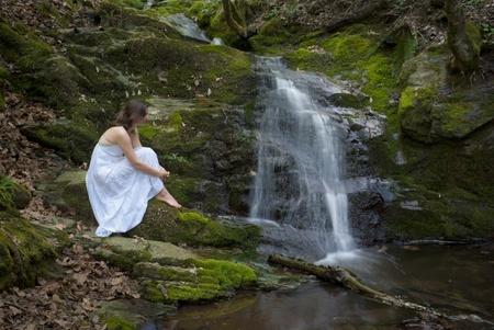 oneness: Bella giovane donna in abito bianco contempla una cascata nel bel mezzo di una foresta