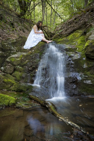 Beautiful young woman in a white dress sits next to a forest waterfall photo