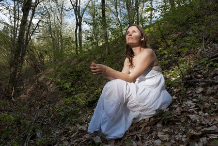 Young woman wearing a white dress sitting on the ground in a forest Stock Photo - 13254350