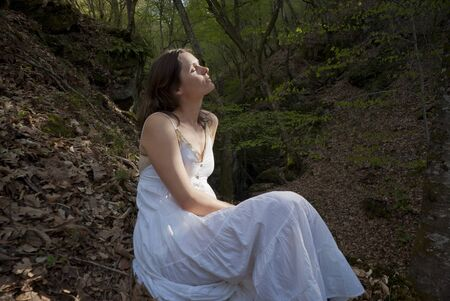oneness: Beautiful young woman sits with eyes closed in a beam of sunlight in the forest Stock Photo