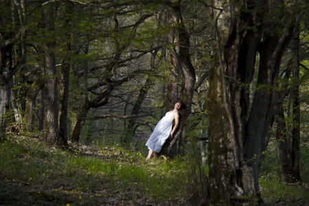 oneness: Young woman wearing a white dress leans on a tree  Stock Photo