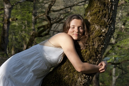 Young woman warmly embraces a tree with love photo