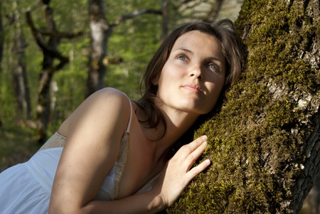 Beautiful young woman rests against a soft tree deep in the forest photo