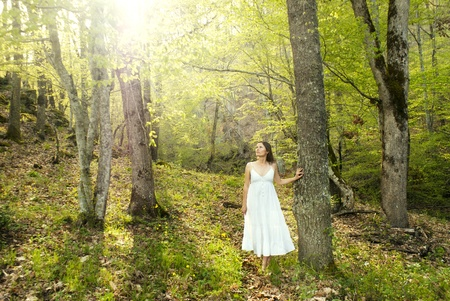 Young woman wearing a white dress explores a magical forest