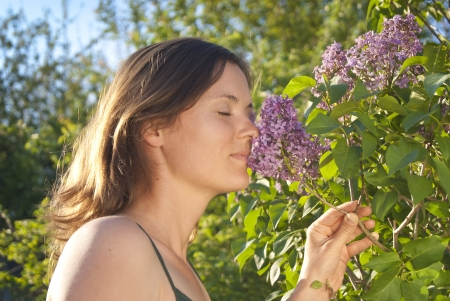 Girl smelling a scented lilac on a sunny day photo