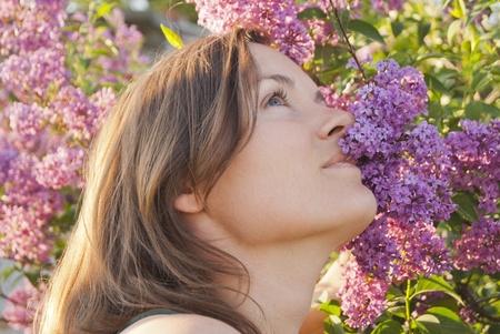 Joven y bella mujer disfrutando de la fragancia de una flor lila
