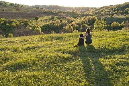 Preciosa mujer joven y su perro guardián puesta de sol juntos