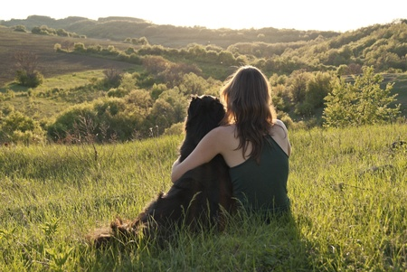 A beautiful young woman hugs her dog as they sit in a field  photo