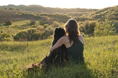mujer con perro: Una mujer joven y hermosa abraza a su perro mientras se sientan en un campo Foto de archivo