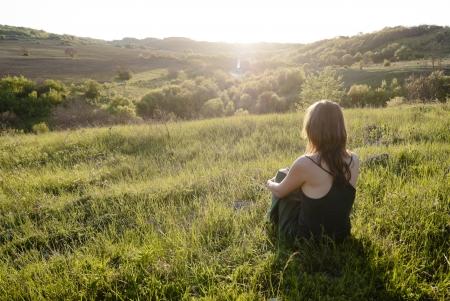 frau denken: Sch�ne junge Frau sitzt auf dem Gras beim Sonnenuntergang im Gr�nen gelegen Lizenzfreie Bilder