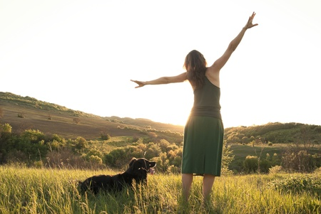 Girl stretches in the sunlight whilst walking her dog photo