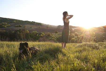 relaxes: Hermosa chica se relaja bajo el sol mientras paseaba a su perro