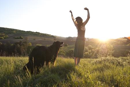 Mooie vrouw heft haar armen aan de zon in vreugde tijdens het lopen haar hond