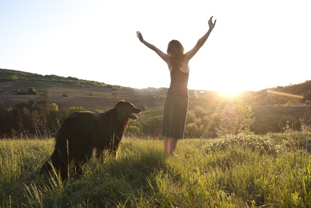 Beautiful young woman raises her arms to the sun whilst walking her dog Stock Photo
