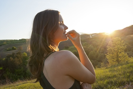 Beautiful young woman chews a piece of grass in the countryside photo