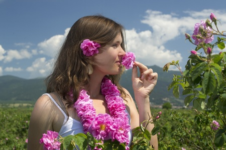 Beautiful girl smelling a rose in a rose field wearing a garland of roses photo