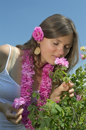 Beautiful girl smelling a rose wearing a garland of roses photo