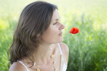 A beautiful, natural young woman with a poppy and a daisychain photo