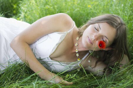 Beautiful young woman lying in a meadow with eyes closed, holding a flower photo