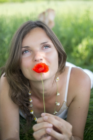 Beautiful young woman holds a poppy whilst daydreaming photo