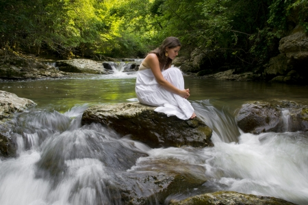 Beautiful young girl enjoying the the clean water of a mountain stream Stock Photo