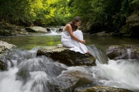 bulgaria girl: Beautiful young girl enjoying the the clean water of a mountain stream Stock Photo
