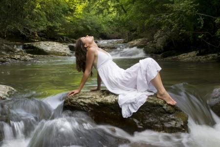 Belle jeune fille jouissant de la purification elle-même dans l'eau claire d'un ruisseau de montagne Banque d'images - 14166222