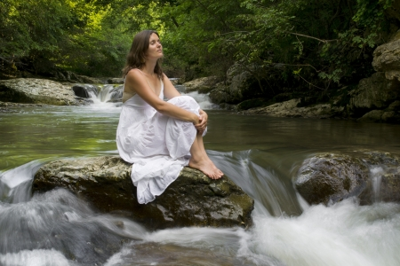 merging together: Beautiful young girl enjoying the purifying herself in the clear water of a mountain stream