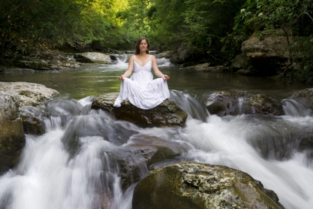 Beautiful young woman meditating surrounded by the purifying waters of a clear mountain stream Stock Photo - 14166220