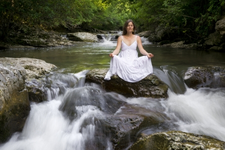 Beautiful young woman meditating surrounded by the purifying waters of a clear mountain stream Stock Photo